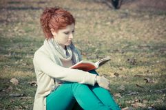 Red long hair girl at the park reading Stock Photography