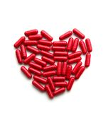 Red long pills in a heart form Royalty Free Stock Images