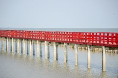Red long timber boardwalk is tourist attraction alongside a waterfront near coastal line in Samut Prakan, Thailand. A beautiful Red long timber boardwalk is stock photography