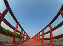 Red long timber boardwalk is tourist attraction alongside a waterfront near coastal line in Samut Prakan, Thailand. A beautiful Red long timber boardwalk is stock image