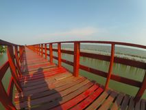 Red long timber boardwalk is tourist attraction alongside a waterfront near coastal line in Samut Prakan, Thailand. A beautiful Red long timber boardwalk is stock images