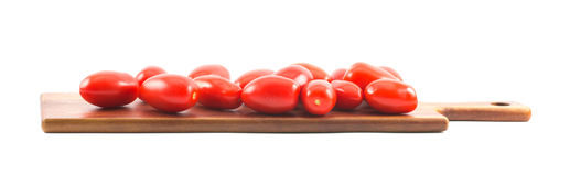 Red long tomatoes on a wooden board and white background.  royalty free stock photography