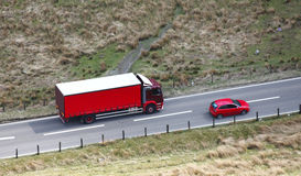 Red lorry. Aerial view of a red lorry and trailer driving on a road in this logistics / haulage and transport concept royalty free stock photography