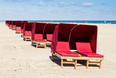 Red lounges on a beach Stock Image