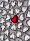 Red Love. A red chocolate heart in a sea of silver hearts Royalty Free Stock Photos