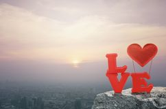 Valentines day concept. Red love alphabet and fabric heart ballon on rock over aerial view of cityscape at sunset, vintage style, Valentines day concept Royalty Free Stock Images