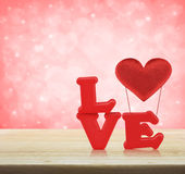 Red love alphabet and fabric heart on wooden table over light pi Stock Photos