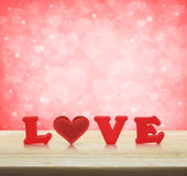 Red love alphabet and fabric heart on wooden table over light re Stock Photos