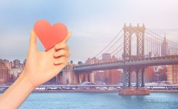 Hand hold red heart over Brooklyn Bridge  New York. Red love heart and on background Brooklyn Manhattan Bridge on a winter foggy day in New York, USA stock image