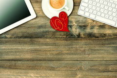 Red love heart, tablet pc, coffee. Valentines Day workplace. Red love heart, tablet pc, keyboard and coffee on wooden table. Valentines Day workplace. Retro Royalty Free Stock Photo