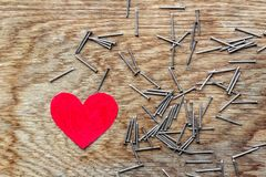 Red heart on wooden background surrounded by iron nails. Red love heart on wooden background surrounded by iron nails royalty free stock photo