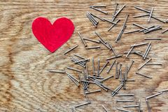Red heart on wooden background surrounded by iron nails with copy space. Red love heart on wooden background surrounded by iron nails stock images