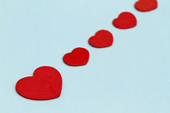 Red love hearts. Row of red love hearts receding on light background Stock Photography