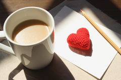 Red love hearts on brown paper note with a cup of coffee. Royalty Free Stock Photography