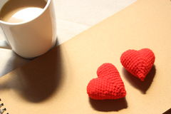 Red love hearts on brown paper note with a cup of coffee. Stock Images