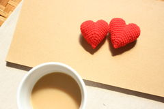 Red love hearts on brown paper note with a cup of coffee. Royalty Free Stock Image