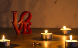 Red love letters on white background on the left wiht two rings and candles stock images