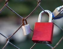 Red love lock attached to wire fence next to a rusty lock. A love lock painted red attached to a wire fence next to a smaller rusty lock royalty free stock image