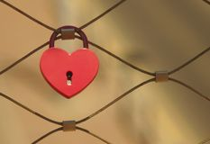 Red love lock on a bridge. Close-up of a heart-shaped red love lock hanging on a metal bridge railing on a blurred background stock image