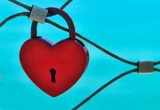 Red love lock in front of blue sky. Close-up of a heart-shaped red love lock hanging on a bridge railing in front of the bright blue sky stock image