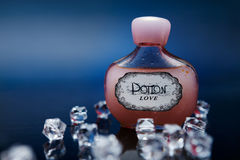 Red love potion in a bottle with crystals. On dark blue background royalty free stock photos