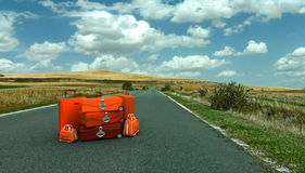 Red luggage in the middle of the road Stock Image