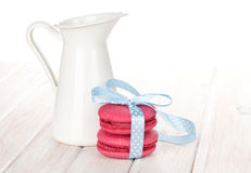 Red macarons with blue ribbon and milk jug Royalty Free Stock Images