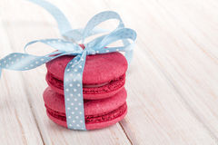 Red macarons with blue ribbon. On white wooden table royalty free stock image