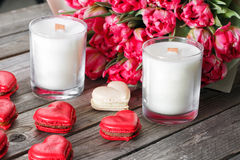 Red macaroons desserts and tulips on wooden background. dessert for breakfast on Valentine`s Day.  royalty free stock photo