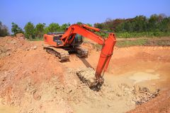 Red machinery digging red soil is big hole on blue sky. And green tree background outdoor stock photos