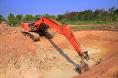 Red machinery digging soil is big hole on blue sky. And green tree background outdoor stock photo