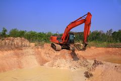 Red machinery digging soil is hole on blue sky. And green tree background outdoor royalty free stock image