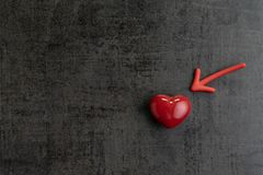 Red magnet arrow pointing to shiny ceramic red heart shape on cement chalkboard wall, minimal concept for Happy Valentine`s day. In February stock image