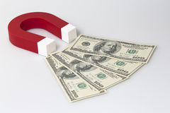 Red magnet attracts dollar banknotes. Royalty Free Stock Photos