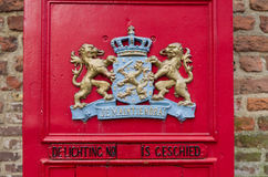 Red mail box. Part of a traditional red mailbox with the official weapon of the kingdom of the Netherlands on it Stock Image