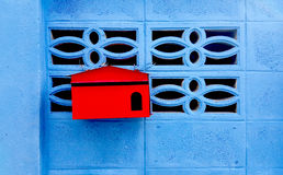 Red mailbox on the blue wall house Stock Photo