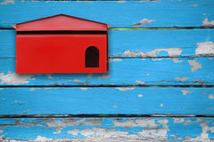 Red mailbox with blue wood Royalty Free Stock Photo