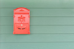 Red mailbox with green wood Royalty Free Stock Photos