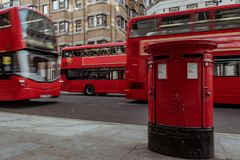 Red mailbox in London with double decker bus passing by stock photos