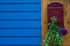 Red mailbox. With violet flower and green leaf near blue wall Stock Photography