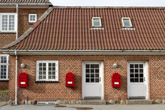 Red mailboxes on stone walled house Stock Image