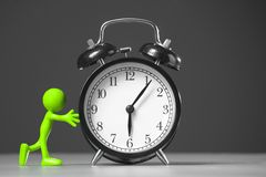 Red man and an alarm clock. Green man pushing an alarm clock. The concept of time Stock Image