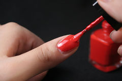 Red manicure. Lady applying red enamel on her nails Stock Photography