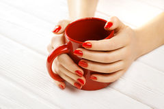 Red manicure with a cup of tea. Beautiful red manicure with a cup of tea on the white wooden table Royalty Free Stock Images