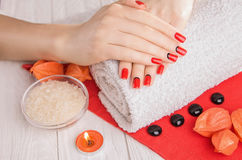 Red manicure with dekor and towel on white wooden table. Royalty Free Stock Photography