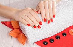 Red manicure with dekor and towel on white wooden table. Stock Photography
