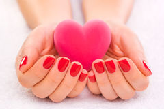 Red manicure with gift box on the white towel Stock Images