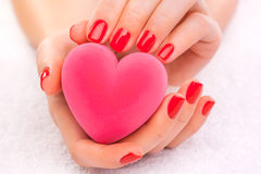 Red manicure with gift box on the white towel Royalty Free Stock Photography