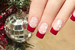 Red manicure. Red nail Polish on artificial nails with white crumb and new year's accessories Stock Images