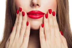 Red manicure nails and red female lips closeup.  stock photos